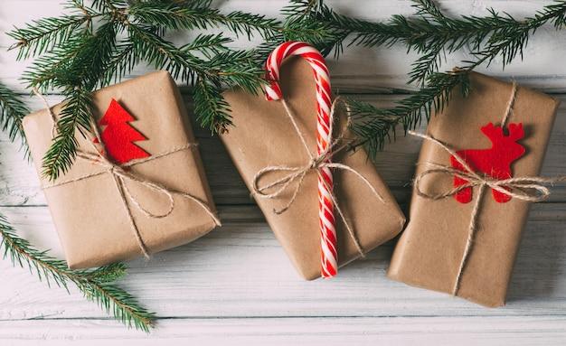 クリスマスツリーの枝を持つテーブルの上のクリスマスギフトボックス