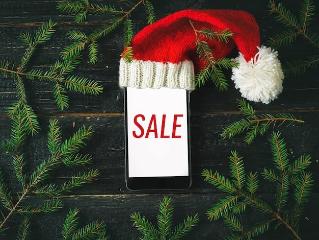 画面と暗い木のクリスマス帽子の碑文販売とスマートフォン