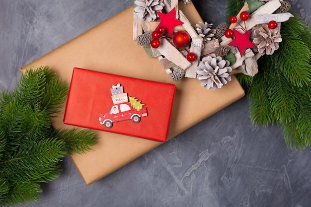 クリスマスの組成物。ギフトボックス、モミの木、サンタと木製のおもちゃの車、テキストクリスマス。概念。平干し、コピースペース