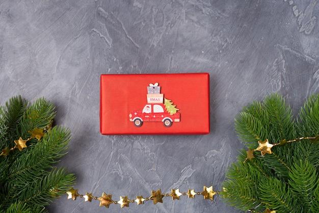 クリスマスの背景。ギフトボックス、モミの木、サンタと木製のおもちゃの車、テキストクリスマス。概念。平干し、コピースペース
