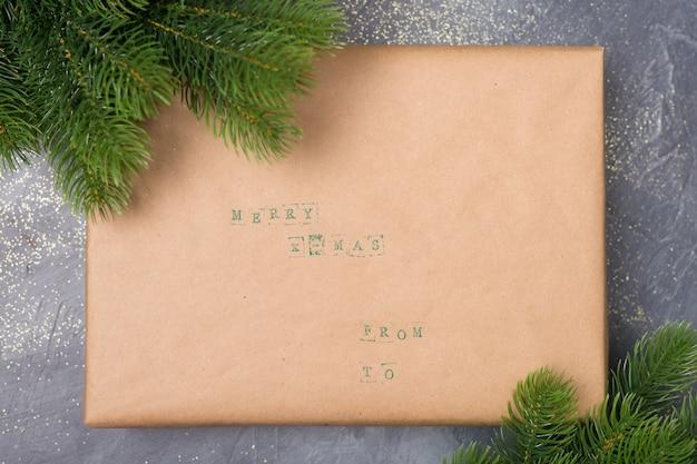 クラフト紙、暗い背景上の枝で飾られたクリスマスギフトボックス。メリーグリーティングカード。冬の休日のテーマ。