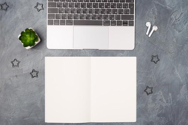 Плоский серый рабочий стол с серебристым ноутбуком, наушниками, списком бумаги и канцелярскими принадлежностями