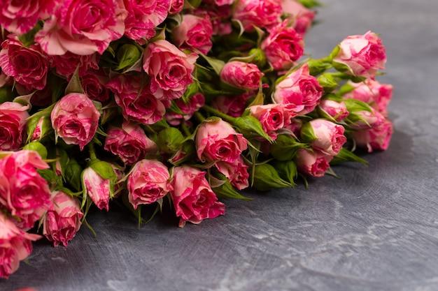 灰色の背景にピンクのスプレーバラ。上面図。コピースペース。誕生日の女性の日母の聖バレンタインの日のコンセプト