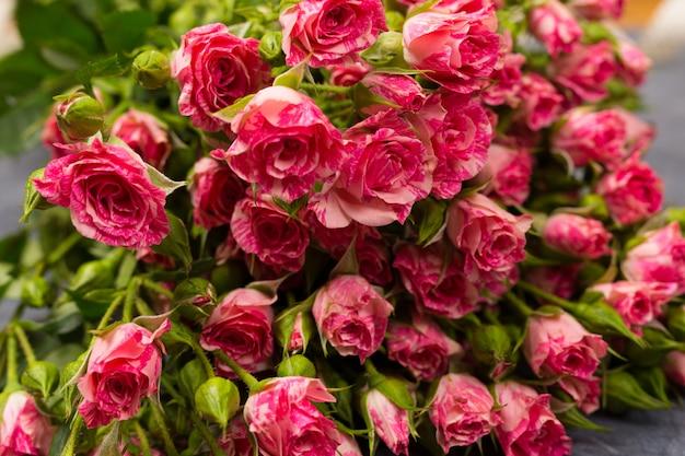 灰色の背景にピンクのスプレーバラ。コピースペース。誕生日の女性の日母の聖バレンタインの日のコンセプト