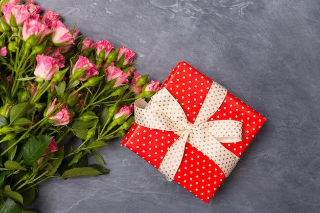 灰色の背景に赤いボックスでクローズアップピンクスプレーバラギフト女性の日母の聖バレンタインの日の概念コピースペース