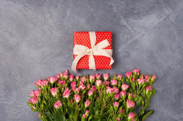 ピンクのスプレーバラ、灰色の背景に赤いボックスにギフト。女性の日母の聖バレンタインのコンセプトコピースペース