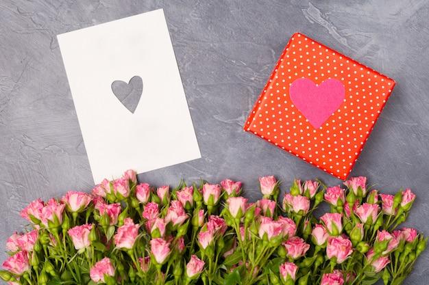 Розовые розы, подарок в красной коробке и открытка с сердцем на сером фоне.