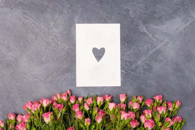 Розовые розы и подарочная белая открытка с сердцем на сером фоне день женщины концепция мамы на день св. валентина