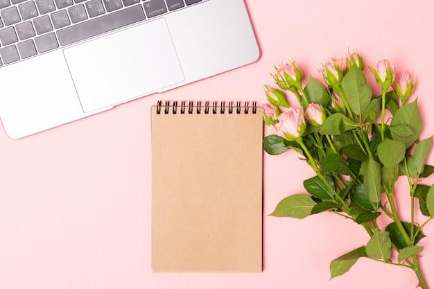 С розовыми розами и пустой коричневый ремесло ноутбука. минималистский плоский лежал, розовый фон.