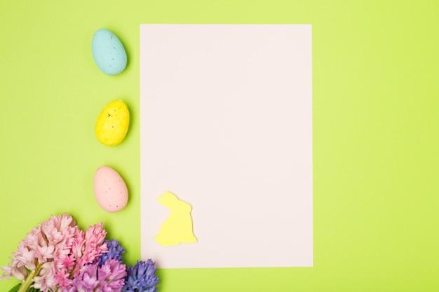 Пасхальная композиция с гиацинтами, яйцами, кроликом и чистым листом бумаги. фон. пасхальная концепция.