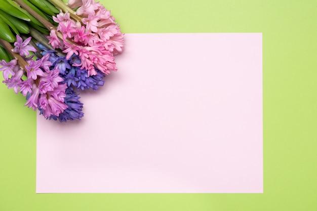 ヒヤシンスとピンクの空白の紙の花の組成。春の花の背景。イースターのコンセプト。平干し、