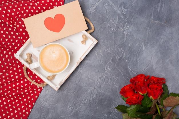 バレンタインデーのコンセプト。朝のコーヒー、赤いハートの封筒、灰色の机の上のバラ。フリースペース。テキスト用のスペース。