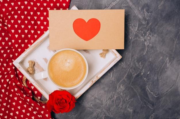 閉じる。バレンタインデーのコンセプト。朝のコーヒー、心の封筒、灰色の机の上のバラ。フリースペース。テキスト用のスペース。