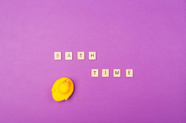 木製の手紙バスタイムとゴム製の黄色いアヒルの紫色の背景。上面図。平干し。バス子テーマコンセプト。