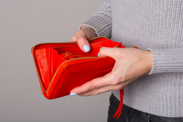 彼の手に女性の財布のクローズアップ。灰色の背景にフリースペース。