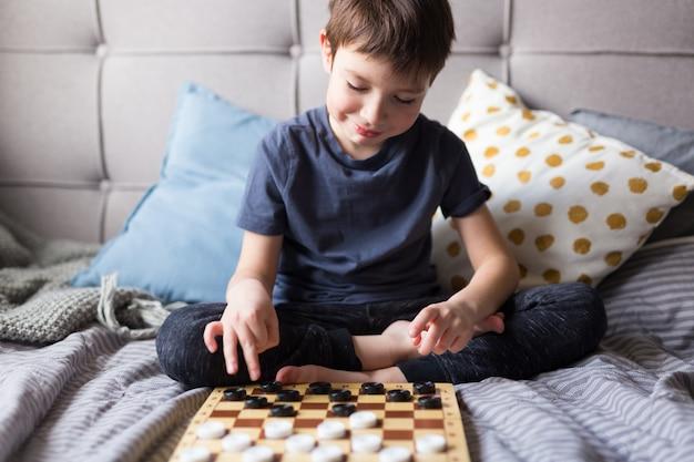 若い子供の手がベッドの上のチェッカーテーブルゲームをプレイします。家にいる検疫の概念。ボードゲームと子供のレジャーのコンセプトです。家族の時間。