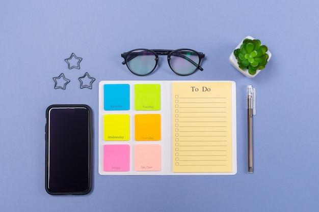 Вид сверху пустой список дел на неделю, ручка, очки и сотовый смартфон на светло-фиолетовом фоне, плоская планировка. копировать пространство свободное место. график. расписание уроков.