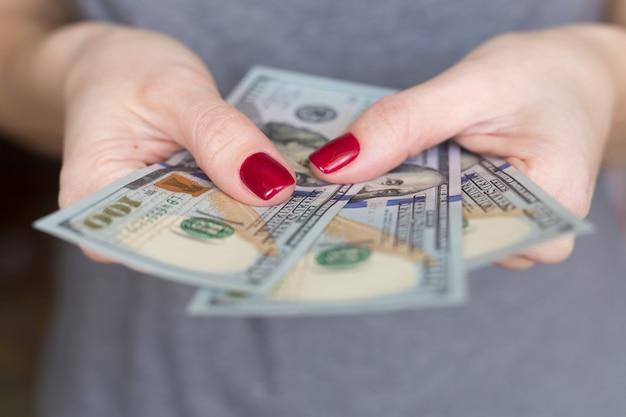 Доллары сша банкноты. деньги в женской руке.