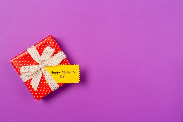 グリーティングカードとテキスト紫色の背景に幸せな女性の日と赤いギフトプレゼントボックス。フリースペース。テキストのスペースをコピーします。母の日のコンセプトです。フラット横たわっていた。上面図。