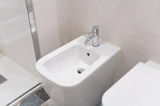 Белое биде прикручивается к бежевой изразцовой стене в ванной, крупный план. белое биде с хромированной мешалкой на кафельном полу