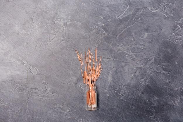 灰色の背景、ツール建設機器コンセプトのガラス瓶からクーパー金属釘。フリースペース。コピースペース。