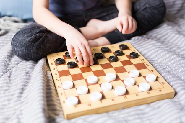 若い子供はベッドの上のチェッカーテーブルゲームを手します。自宅での検疫の概念。ボードゲームと子供のレジャーのコンセプトです。家族の時間。