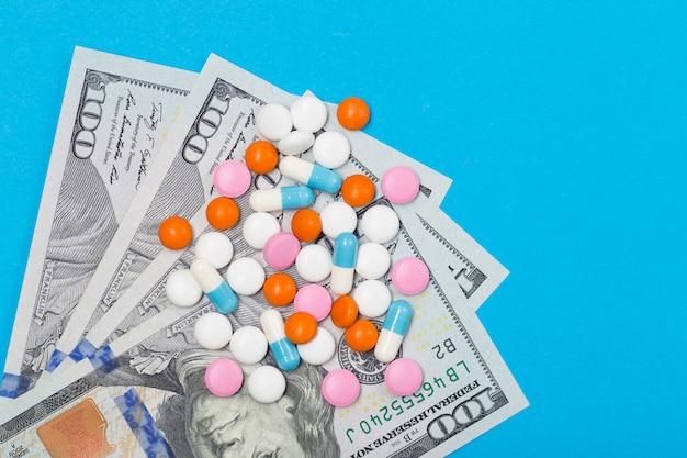 Таблетки, таблетки и капсулы на фоне долларов сша. свободное место. концепция здравоохранения