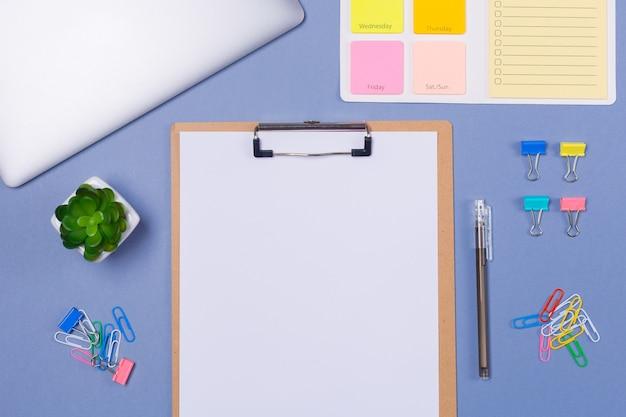 Вид сверху пустой список в буфер обмена, чтобы сделать список на неделю, ручка, канцелярские принадлежности и ноутбук на светло-фиолетовом фоне, плоская планировка. копировать пространство свободное место. график. расписание уроков.
