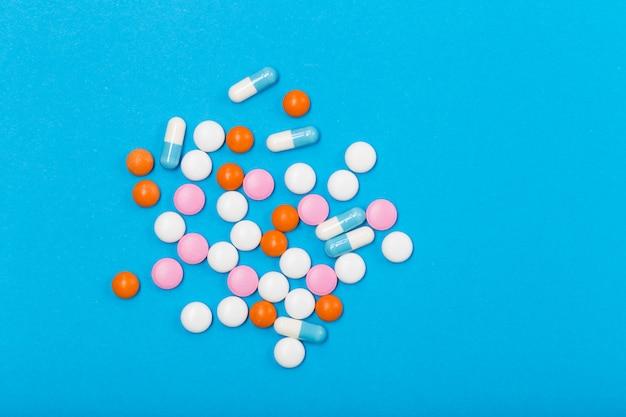 Ассорти из фармацевтической медицины таблетки, таблетки и капсулы на синем фоне. свободное место. концепция здравоохранения.