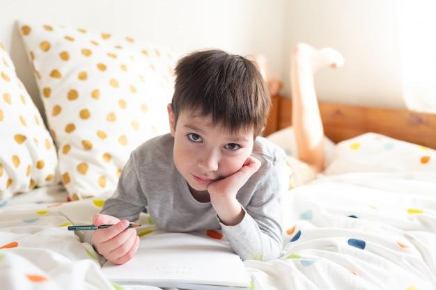 ベッドの上の学校の男の子と自宅で学校の宿題をして、ノートに書きます。オンライン教育の遠隔学習。検疫