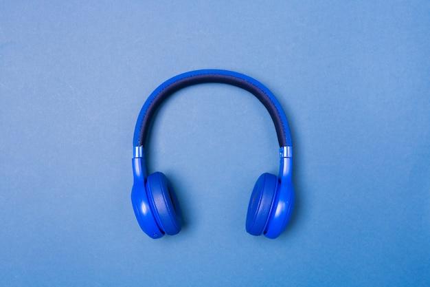 青い背景、上面に青いヘッドフォン。コピースペース。テキストのためのスペース。