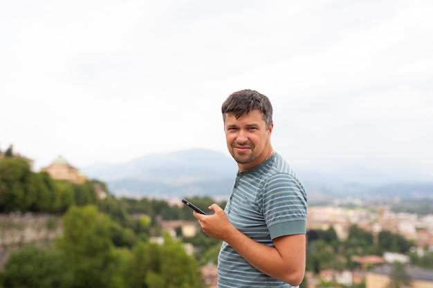 町でモバイルスマートフォンでカメラで見て幸せな笑みを浮かべて男。旅行の概念。トラベラー。夏休み。