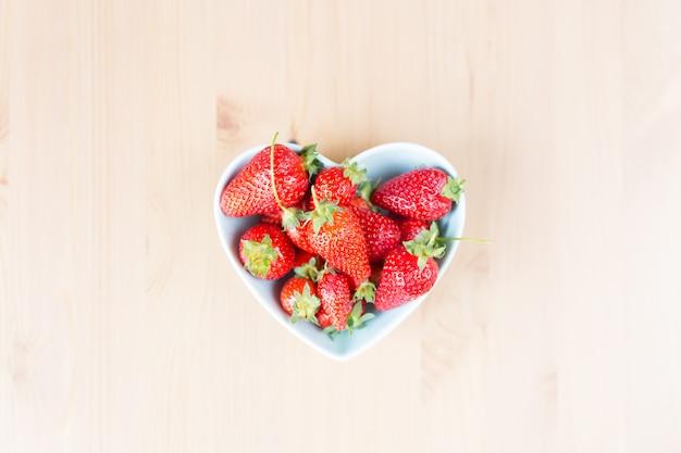 Взгляд сверху близкое вверх шара сформированного сердцем свежей клубники на таблице.