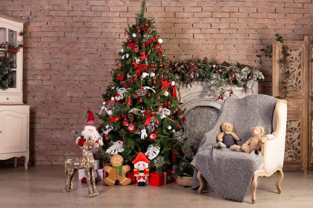 カラフルなボールとレンガの壁の上のギフトボックスクリスマスツリー。新年クリスマスのコンセプトです。デコレーション室内の写真インテリア。