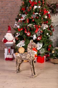 クリスマスツリーの前で木の馬。フリースペース。スペースをコピーします。