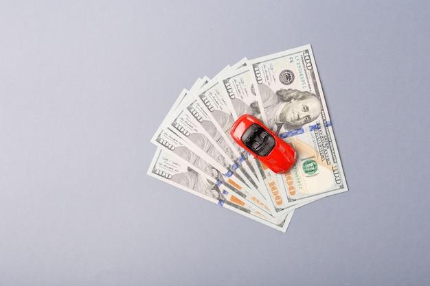 上面図。お金のドルの山の上の小さな赤い車。自動車ローンのコンセプトです。レンタカー貯蓄フリースペース。スペースをコピーします。