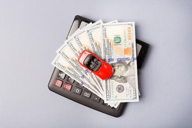 電卓とお金のドルの山の上の小さな赤い車。自動車ローンのコンセプトです。レンタカー貯蓄フリースペース。スペースをコピーします。