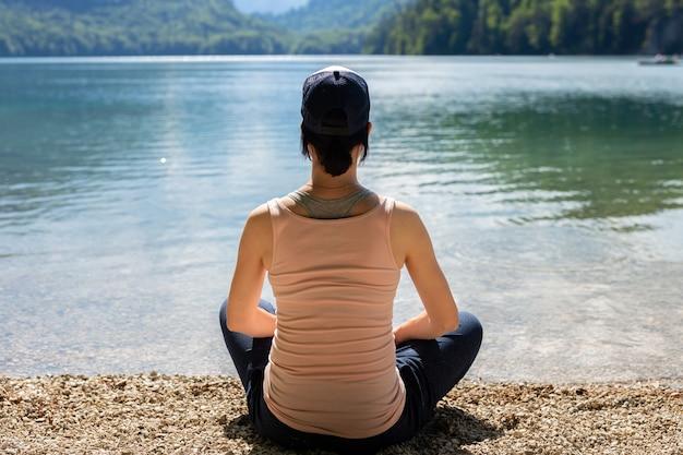 砂の上に座って、湖を探している若い女性