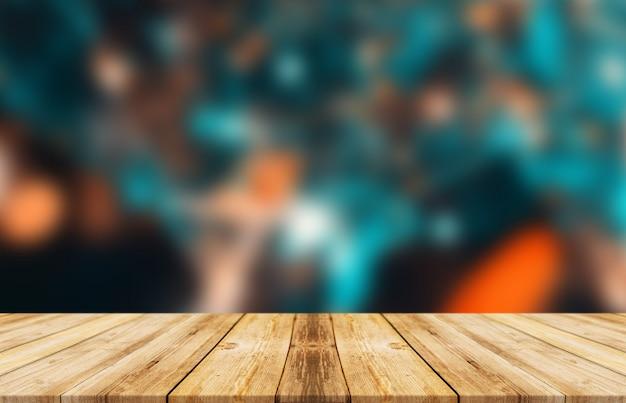 カラフルなぼかしの背景を持つ空の木製テーブル