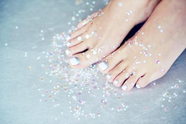 色のペディキュアと女性の足