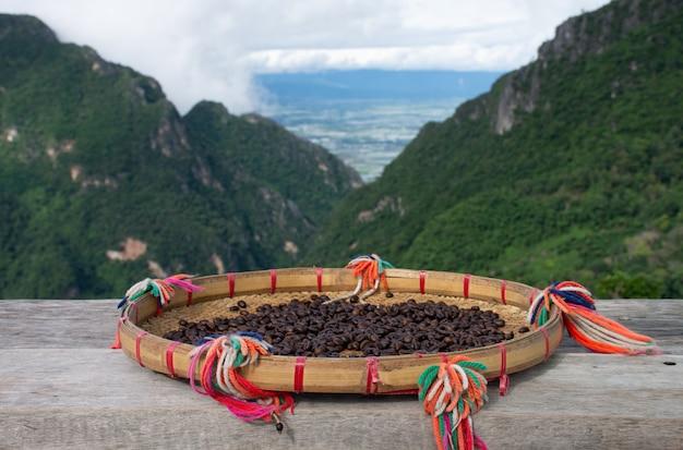 タイ北部の美しい山の景色を望む木製のテーブルで天日干しした生のコーヒー豆。