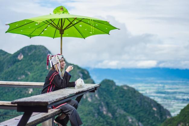 アジアの女性は山の頂上でお茶を飲みます。