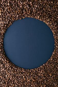 黒の背景にコーヒー豆から作られたラウンドフレーム。垂直配置上面図。テキスト用のスペースをコピーします。