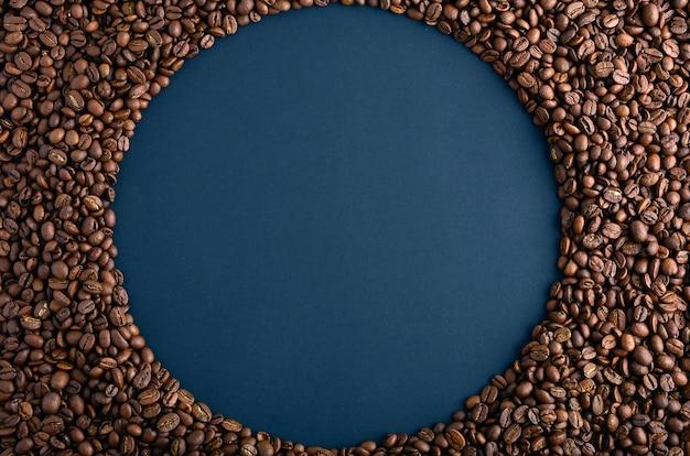 黒の背景にコーヒー豆から作られたラウンドフレーム。水平配置上面図。テキスト用のスペースをコピーします。