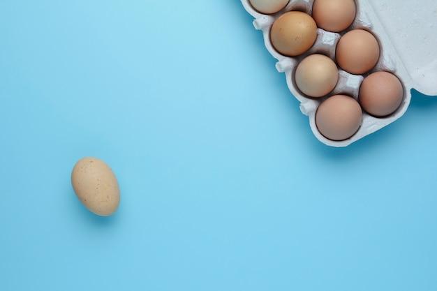 青いテーブルの上の卵ボックスで鶏の生卵のトップビュー