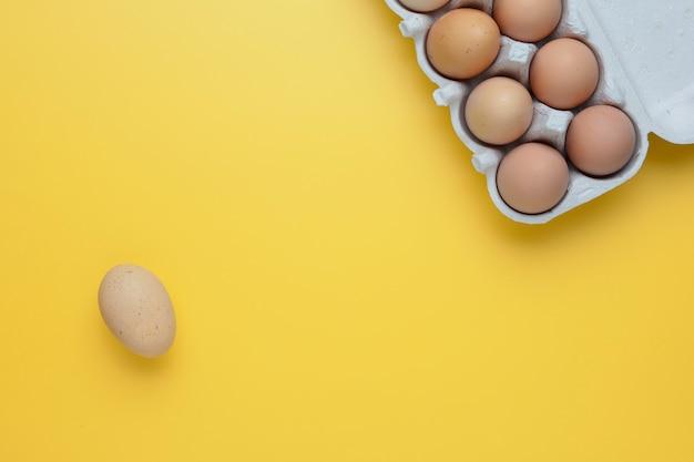 黄色の背景に卵ボックスで鶏の生卵のクローズアップビュー
