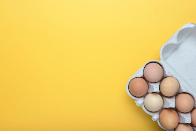 黄色の背景のトレイに鶏の卵。上からの眺め。テキストのための場所