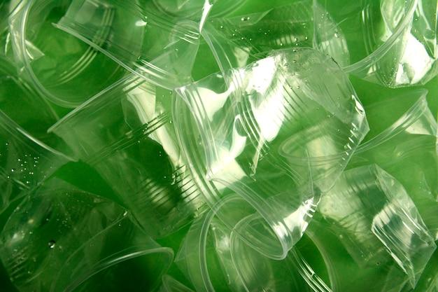 緑色の背景で、リサイクルの概念、ミニマルなデザインに使用されるプラスチック製のコップ