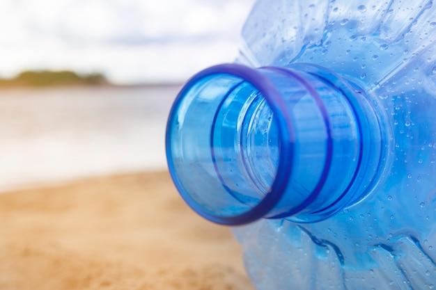 プラスチック廃棄物。大きなボトルの首。閉じる。環境汚染