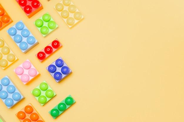 おもちゃのブロック。子供向けゲームの背景。黄色の子供のコンストラクター。マルチカラーキューブ。記憶と心を発達させる運動のためのゲーム。